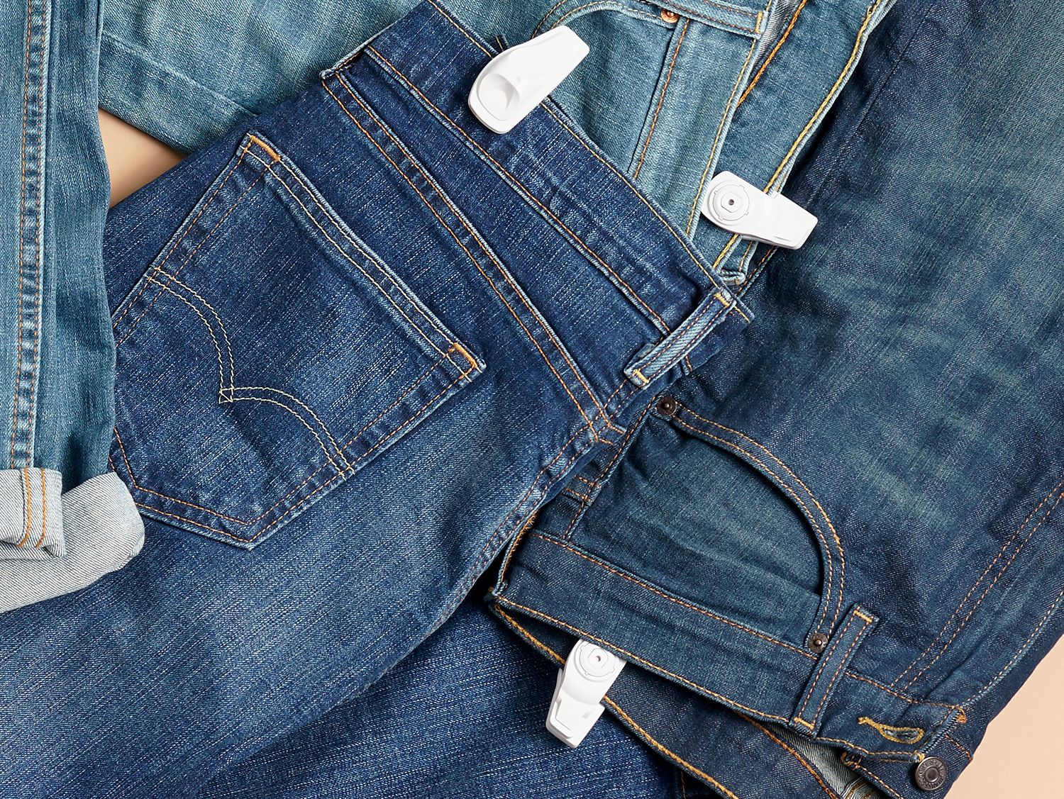 pairs of jeans on a surface with infuzion hard tags