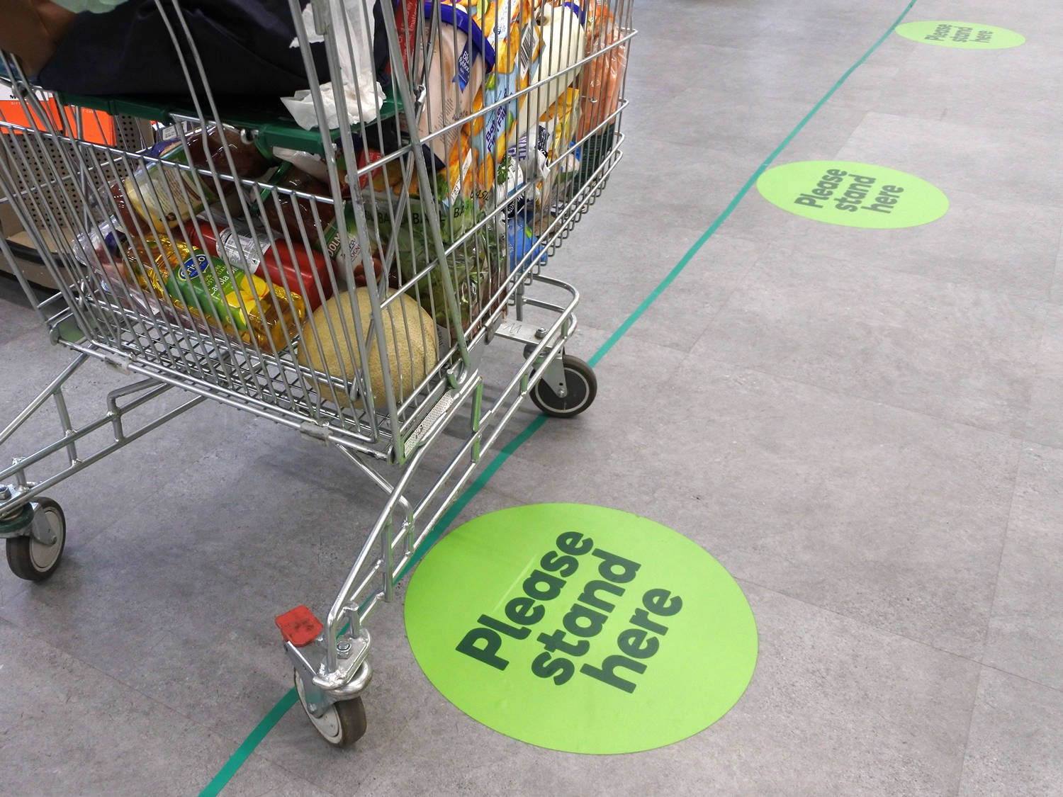 shopping cart in store with social-distancing markers