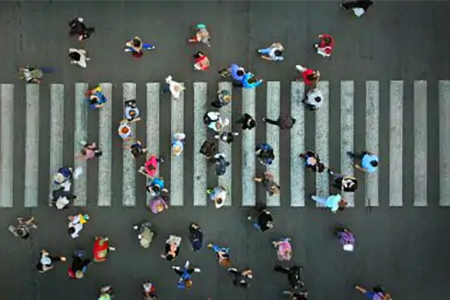 overhead shot of people crossing city street
